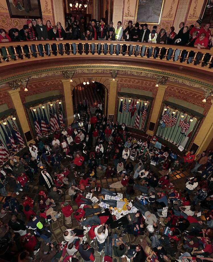 Demonstrators stage a sit-in in the rotunda of the Capitol in Lansing, Michigan, U.S., on Tuesday, Dec. 11, 2012. Michigan lawmakers approved bills to prohibit mandatory union dues in workplaces as thousands of chanting protesters thronged the Capitol. Photographer: Jeff Kowalsky/Bloomberg Photo: Jeff Kowalsky, Bloomberg