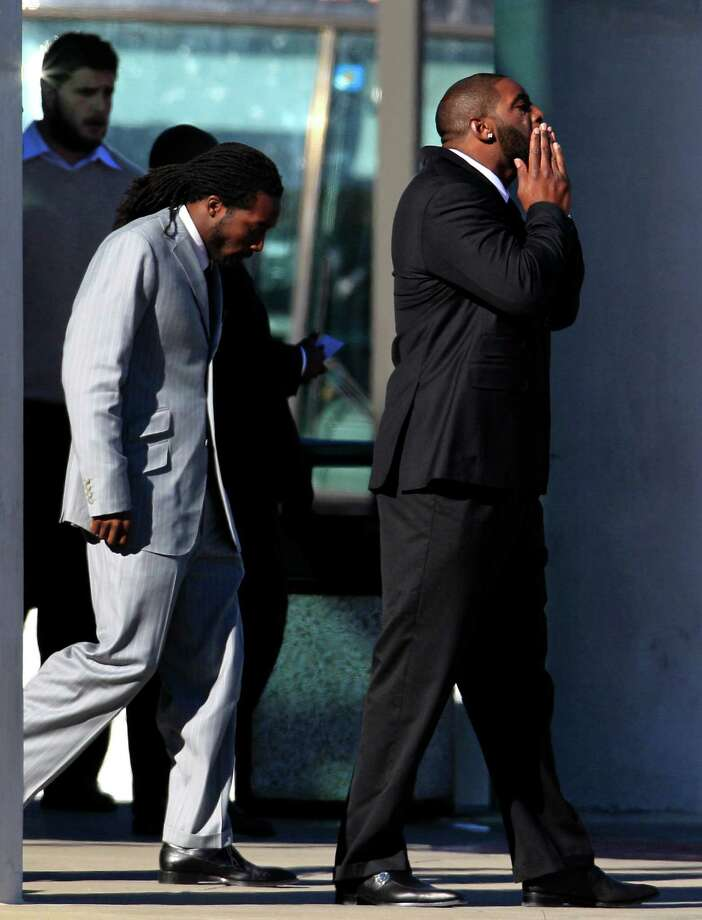 Dallas Cowboys' Mike Jenkins, left, and Jay Ratliff, right, leave a memorial service for practice squad member Jerry Brown at Oak Cliff Bible Fellowship, Tuesday, Dec. 11, 2012, in Dallas. Brown died in a suspected drunken-driving accident on Saturday.  Josh Brent, a teammate, was the driver and is charged with intoxication manslaughter. (AP Photo/LM Otero) Photo: LM Otero, Associated Press / AP