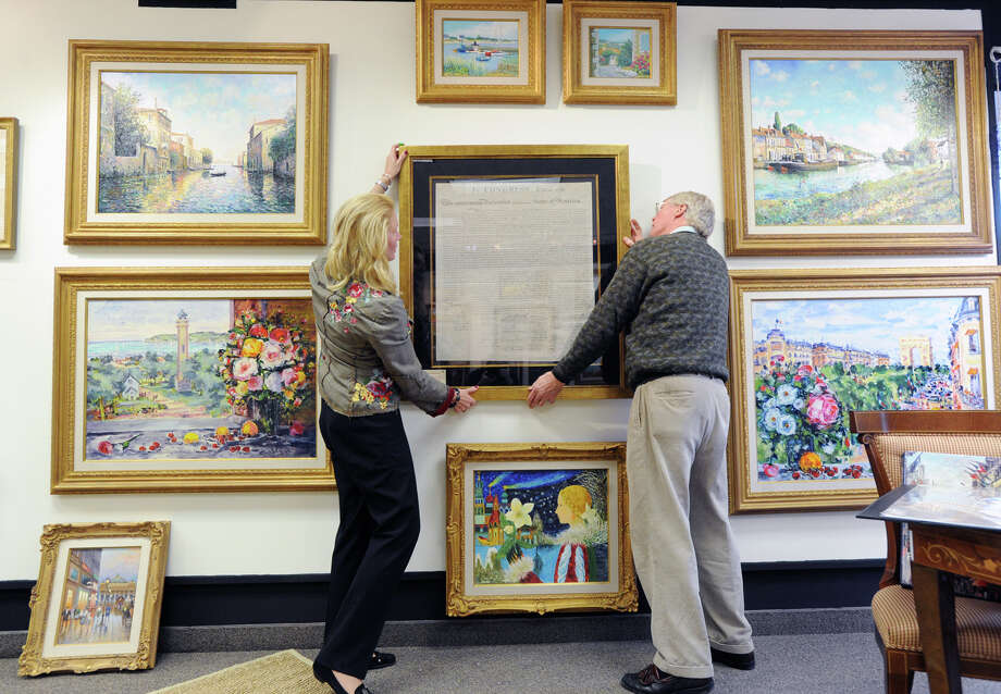 "Tiffany Benincasa, left, and Stephen Rockwell Desloge, mount an engraving of the Declaration of Independence at the C. Parker Gallery in Greenwich, Tuesday afternoon, Dec. 11, 2012. C. Parker Gallery, Seth Kaller, John Reznikoff and Stephen Rockwell Desloge will be hosting the opening of a special showing of ""History You Can Own,"" a collection of authentic historic documents and items from American history available for purchase for the holidays, Wednesday, from 6-8 p.m. at the C. Parker Gallery. The declaration is part of the showing with an asking price of $48,000. Photo: Bob Luckey / Greenwich Time"