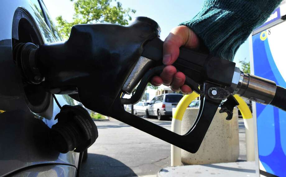 (FILES)A woman pumps gas into a vehicle in this March 2, 2012 file photo in Los Angeles,California. With President Barack Obama's election chances being damaged by rising gasoline prices, the White House was to release a report March 12, 2012 showing progress in weaning America off foreign oil. The report says the United States cut imports of oil from abroad by 10 percent last year, and also touts a rise in domestic production, new energy efficiency standards for cars and renewable energy projects. The White House effort came as a new Washington Post/ABC News poll said Obama's recent gains in popularity were being undermined by rising gasoline prices, despite more positive news from the jobs market. AFP PHOTO/Frederic J. BROWN (Photo credit should read FREDERIC J. BROWN/AFP/Getty Images) Photo: FREDERIC J. BROWN, Staff / AFP