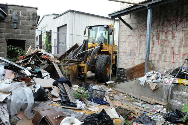 "A payloader starts to romove trash from a blighted property at 121 George Street, in Bridgeport, Conn. Oct. 15th, 2012. The property is the first targeted for cleanup as part of the city's ""Help Fight Blight"" campaign. Photo: Ned Gerard / Connecticut Post"