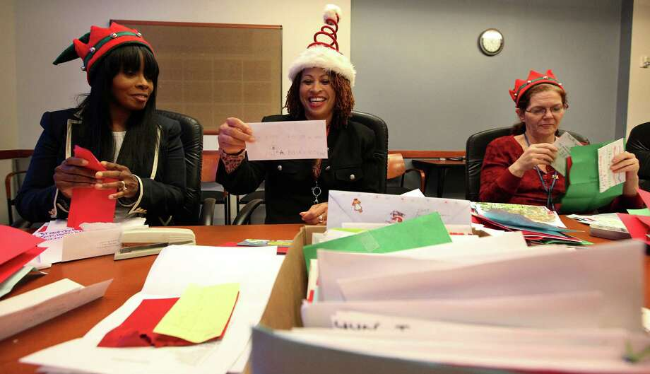 Dionne Montague, left, and Tara Woods get a smile from a child's drawing Tuesday while fellow volunteer Michelle Barrow Degomez sorts letters to Santa from the Beaumont and Houston areas. The public can now help respond to children's wishes. Photo: Mayra Beltran, Staff / © 2012 Houston Chronicle