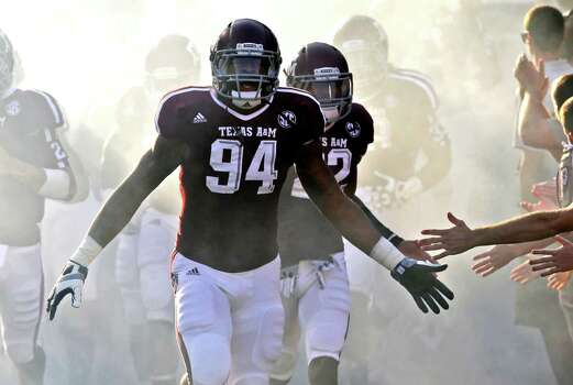 In this photo taken Sept. 22, 2012, Texas A&M's Damontre Moore (94) leads the team out to the field before a college football game against South Carolina State in College Station, Texas. The junior defensive end has shaken off a drug arrest and is now among the nation's leaders in sacks with hopes of an NFL career. (AP Photo/David J. Phillip) Photo: David J. Phillip, Associated Press / AP