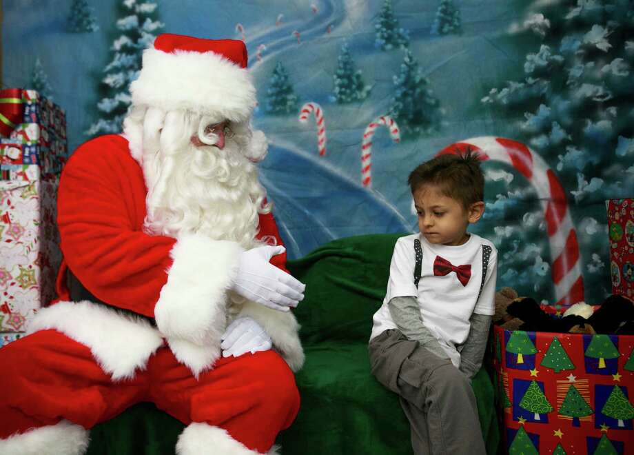 Therapist John Pettingill, dressed as Santa Claus, reaches out to Reece Gonzalez, 5, during the Sensitive Santa Program at Touchstone Behavioral Health in Mesa on Monday, Dec. 10, 2012.  Touchstone Behavioral Health brought its Sensitive Santa to Mesa on Monday and will make him available for free visits by autistic children.  To see Sensitive Santa, children aren't forced to wait in lines, and the environment is quiet and calm. Photo: Charlie Leight, Associated Press / The Arizona Republic
