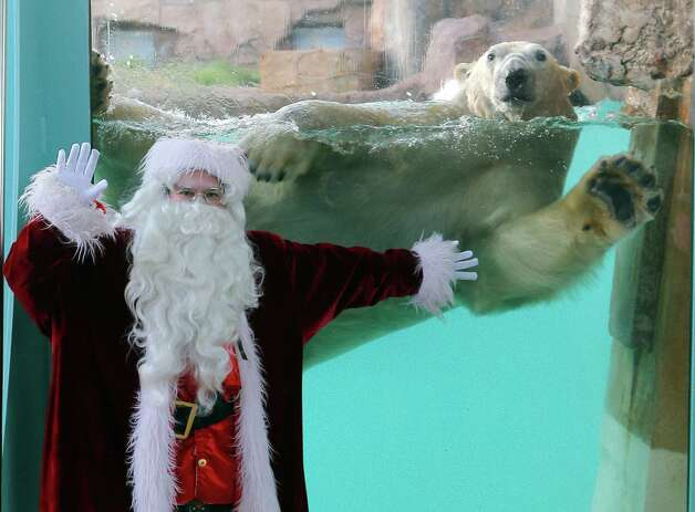 "A man dressed in a Santa Claus costume poses for photographers with a polar bear (Ursus maritimus)  named ""Raspoutine"", at the animal exhibition park Marineland in Antibes, southern France, Tuesday, Dec. 11, 2012. Photo: Lionel Cironneau, Associated Press / AP"