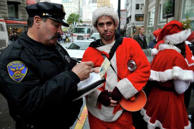 This Dec. 10, 2009 file photo shows a San Francisco Police officer giving a man dressed as Santa Claus an open container ticket during the Santacon pub crawl in downtown San Francisco.  SantaCon is coming to town _ in fact, to nearly 300 towns and cities around the world. Dozens, sometimes hundreds of red-suited revelers gather, bar hop, stop traffic and pose for photos. Photo: Russel A. Daniels, Associated Press / AP