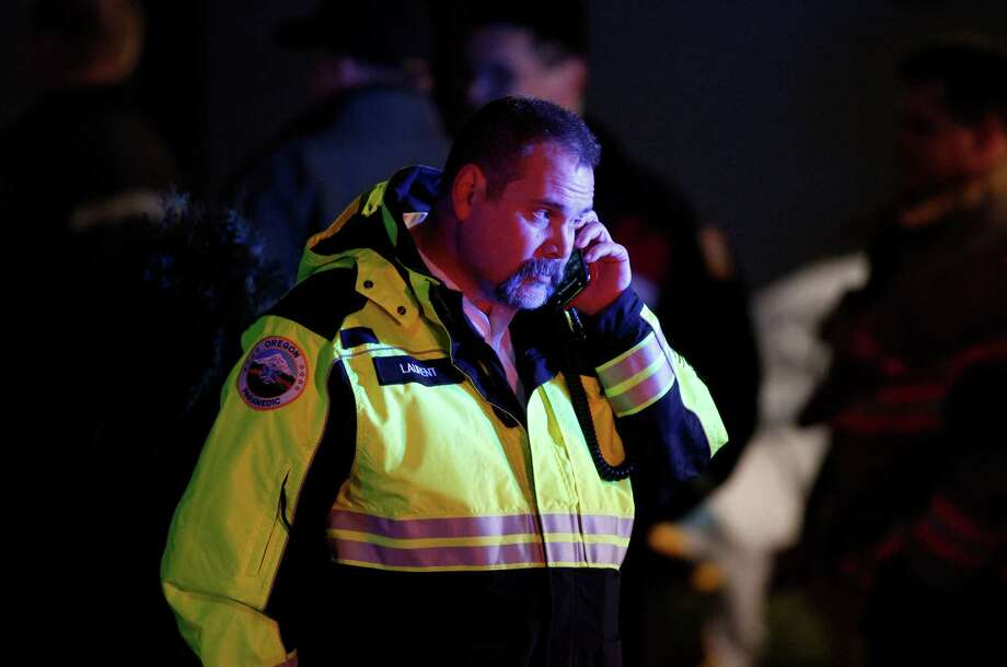 A paramedic talks on the phone outside Clackamas Town Center in Clackamas, Ore., where a shooting occurred Tuesday, Dec. 11, 2012. A gunman opened fire in the Portland, Ore., area shopping mall Tuesday, killing at least one person and wounding an unknown number of others, sheriff's deputies said. Photo: Bruce Ely, Associated Press / The Oregonian