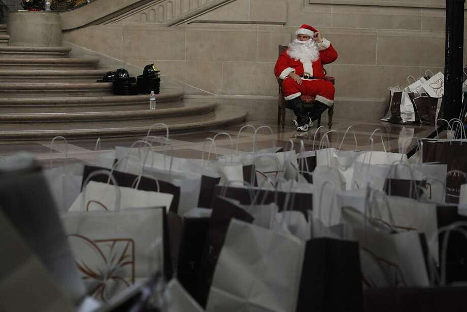 Santa waits to greet children at City Hall, with bags full of gifts that have been donated. They were presented to kids who attended the sixth annual Holiday Children's Toy festival. Photo: Mike Kepka, The Chronicle