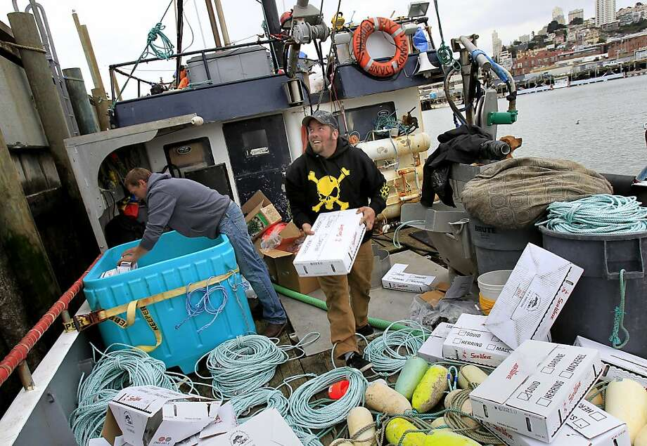 Skipper Russ Deman of the Mandy Jane gathers up bait in preparation for resuming fishing for Dungeness crab. Photo: Brant Ward, The Chronicle