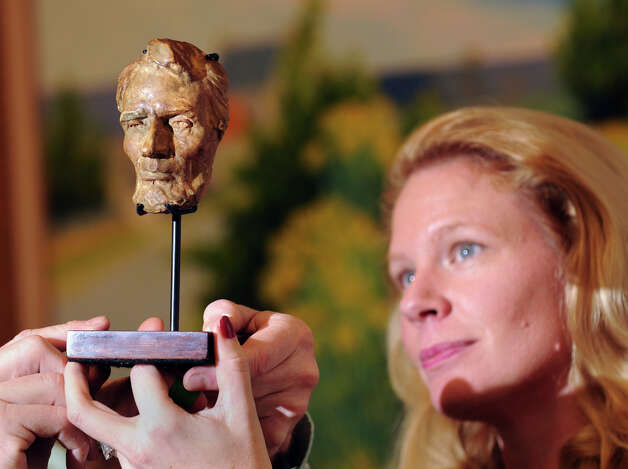 "Tiffany Benincasa of C. Parker Gallery holds up a small plaster bust of Abraham Lincoln that Stamford Connecticut native Gutzon Borglum carried with him while sculpting Mount Rushmore, at the gallery in Greenwich, Tuesday afternoon, Dec. 11, 2012. C. Parker Gallery, Seth Kaller, John Reznikoff and Stephen Rockwell Desloge will be hosting the opening of a special showing of ""History You Can Own,"" a collection of authentic historic documents and items from American history available for purchase for the holidays, Wednesday,  from 6-8 p.m. at the C. Parker Gallery. The bust is part of the showing. Photo: Bob Luckey / Greenwich Time"