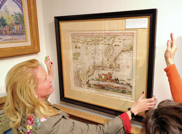 "At left, Tiffany Benincasa of C. Parker Gallery mounts the Last Map of Dutch New York from 1674 on a wall at her gallery in Greenwich, Tuesday afternoon, Dec. 11, 2012. C. Parker Gallery, Seth Kaller, John Reznikoff and Stephen Rockwell Desloge will be hosting the opening of a special showing of ""History You Can Own,"" a collection of authentic historic documents and items from American history available for purchase for the holidays, Wednesday,  from 6-8 p.m. at the C. Parker Gallery. The map is part of the showing and goes for $39,500. Photo: Bob Luckey / Greenwich Time"