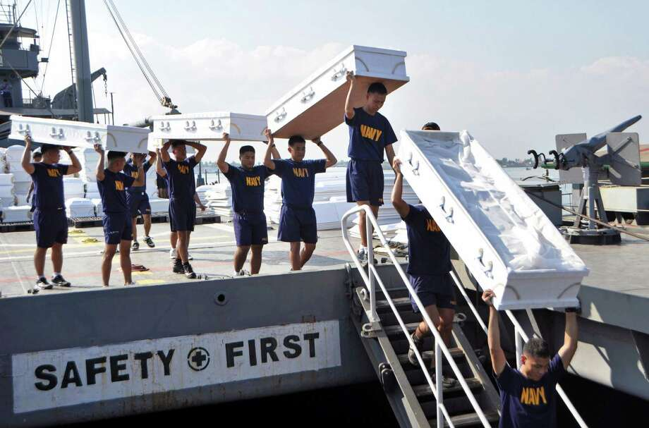 In this photo released by the Philippine Navy, navy personnel carry donated coffins on Philippine Navy ship BRP Laguna (LT-501) at the Sangley Point Naval Base, Cavite province, southern Philippines on Tuesday, Dec. 11, 2012 as it prepares to go to typhoon-affected areas of the country. Typhoon Bopha hit the main southern island of Mindanao last Tuesday, killing hundreds of people, mostly from flash floods that wiped away precarious communities in the southern region unaccustomed to typhoons. Photo: Michael D. Namit, Associated Press / Philippine Navy