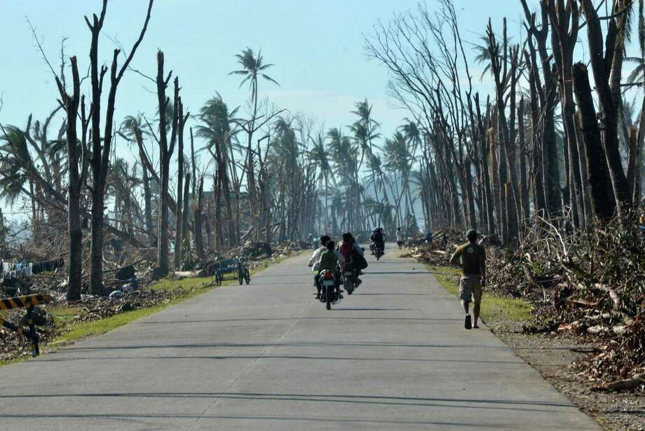 Motorists ride past destroyed trees along a hIghway in Baganga town, Davao Oriental province on December 11, 2012.  The United Nations launched a 65 million USD global appeal on December 10 to help desperate survivors of a typhoon that killed more than 600 people and affected millions in the southern Philippines. Photo: TED ALJIBE, AFP/Getty Images / AFP