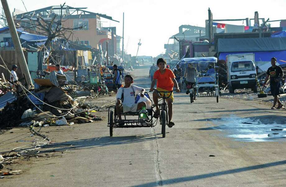 Residents ride on a tricycle past debris littered along a street in Cateel town, Davao Oriental province on December 11, 2012, in the aftermath of Typhoon Bopha. The United Nations launched a 65 million USD global appeal on December 10 to help desperate survivors of a typhoon that killed more than 600 people and affected millions in the southern Philippines. Photo: TED ALJIBE, AFP/Getty Images / AFP