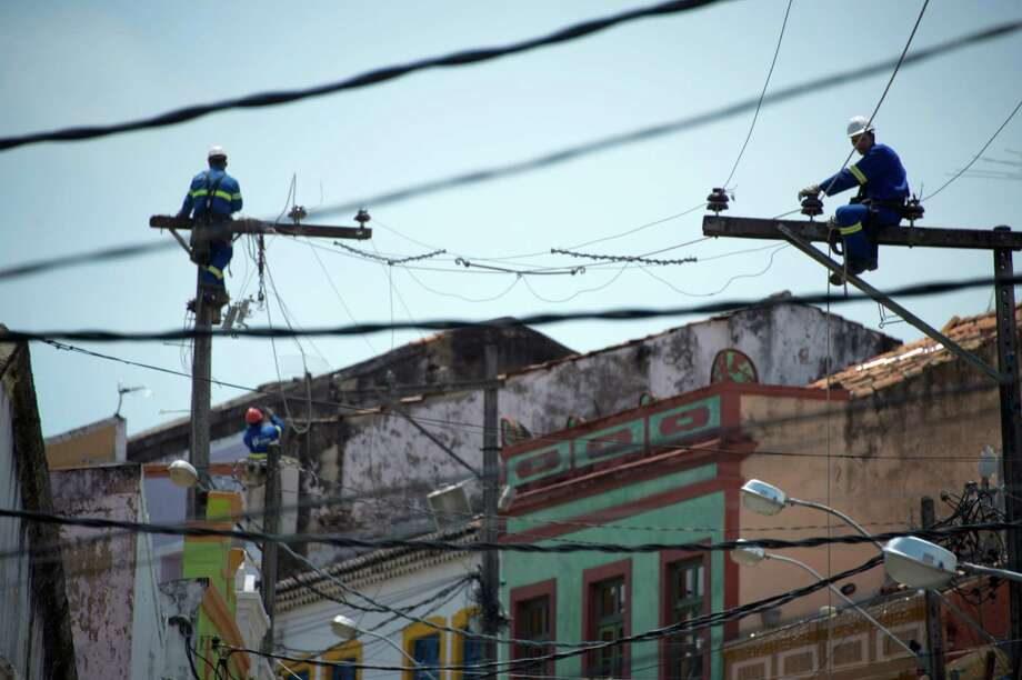 Workers repair an electricity line in Olinda, state of Pernambuco, Brazil, on December 09, 2012. Photo: CHRISTOPHE SIMON, AFP/Getty Images / AFP ImageForum