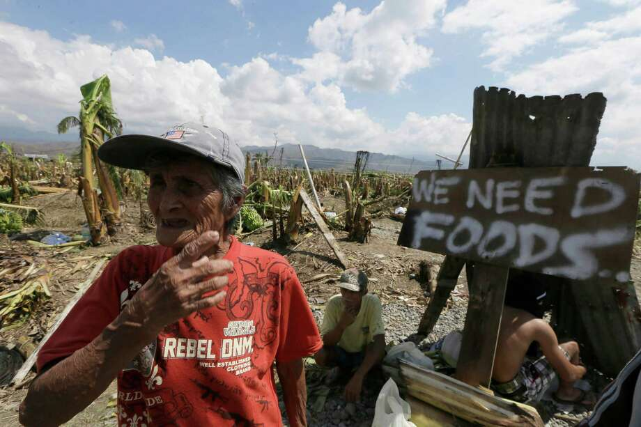 A resident affected by typhoon Bopha begs for aid from passing motorists along a highway at Montevista township, Compostela Valley in southern Philippines Sunday Dec. 9, 2012. The number of missing in the wake of a typhoon that devastated parts of the southern Philippines has jumped to nearly 900 after families and fishing companies reported losing contact with more than 300 fishermen in the South China Sea and Pacific Ocean, officials said Sunday. Photo: Bullit Marquez, Associated Press / AP
