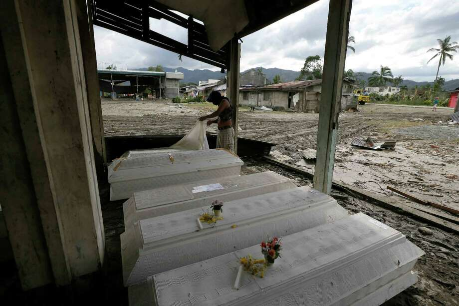 Eddie Jotojot checks the coffin of his son Ejiedev who was killed at the height of Tuesday's typhoon Bopha at New Bataan township, Compostela Valley in southern Philippines Saturday Dec. 8, 2012. Search and rescue operations following a typhoon that killed nearly 600 people in the southern Philippines have been hampered in part because many residents of this ravaged farming community are too stunned to assist recovery efforts, an official said Saturday. Photo: Bullit Marquez, Associated Press / AP