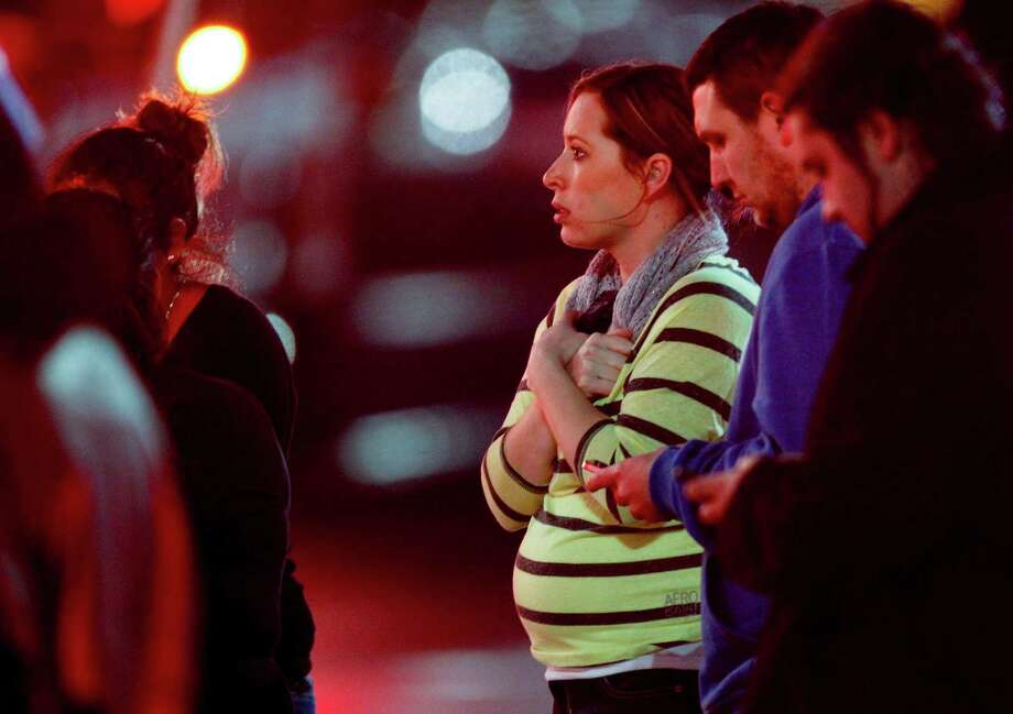 Onlookers observe the scene outside Clackamas Town Center in Clackamas, Ore., where a shooting occurred Tuesday, Dec. 11, 2012. A gunman opened fire in the Portland, Ore., area shopping mall Tuesday, killing at least one person and wounding an unknown number of others, sheriff's deputies said. (AP Photo/The Oregonian, Bruce Ely)  MAGS OUT; TV OUT; LOCAL TV OUT; LOCAL INTERNET OUT; THE MERCURY OUT; WILLAMETTE WEEK OUT; PAMPLIN MEDIA GROUP OUT Photo: Bruce Ely, MBO / The Oregonian