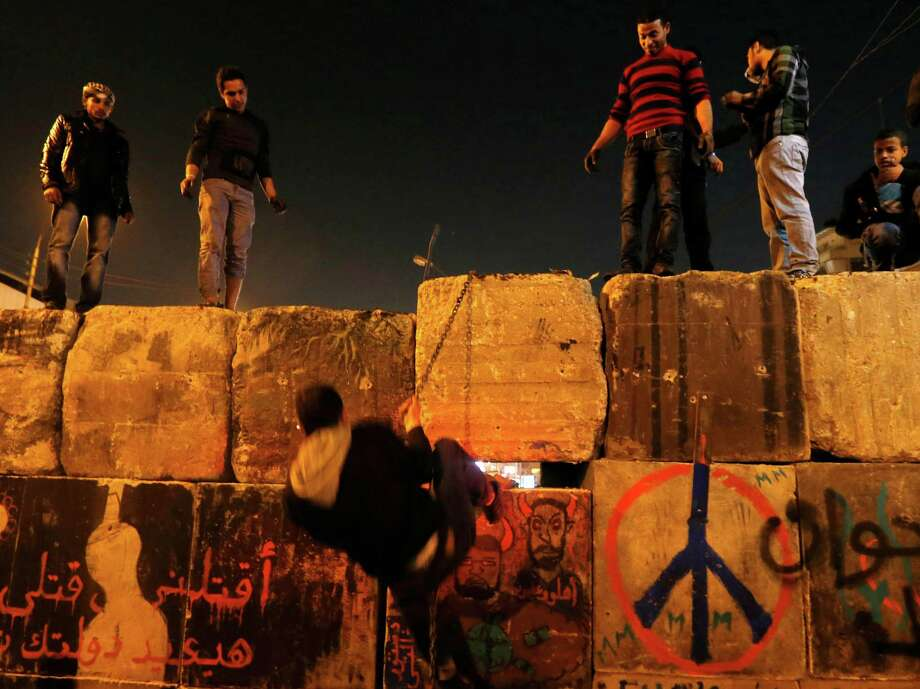 "Protesters dismantle a wall guarding the presidential palace during a demonstration in Cairo, Egypt, Tuesday, Dec. 11, 2012. Arabic writing reads, ""killing me won't bring back your regime."" Thousands of opponents and supporters of Egypt's Islamist president staged rival rallies in the nation's capital Tuesday, four days ahead a nationwide referendum on a contentious draft constitution. (AP Photo/Petr David Josek) Photo: Petr David Josek"