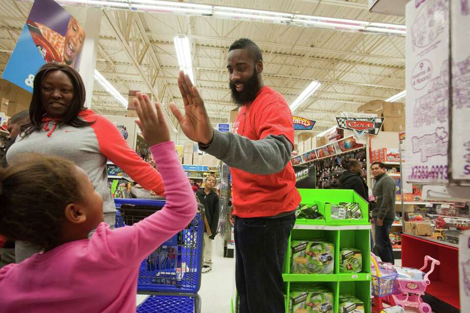 Katie Morgan, 5, gets a high five from Houston Rocket James Harden Dec. 11, 2012 in Houston at Toys R Us. The Houston Rockets Season of Giving program is a holiday tradition bringing together Rockets players, their families and members of the business team, as they host a series of events for members of the community who are less fortunate. Each year, hundreds of children and their families are the recipients of private parties, gifts and surprise visits by Rockets players. Photo: Eric Kayne / © 2012 Eric Kayne