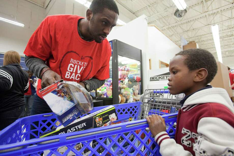 Houston Rockets player Patrick Patterson goes over the selections of Alexander Irankunda, 9, Dec. 11, 2012 in Houston at Toys R Us. Photo: Eric Kayne / © 2012 Eric Kayne