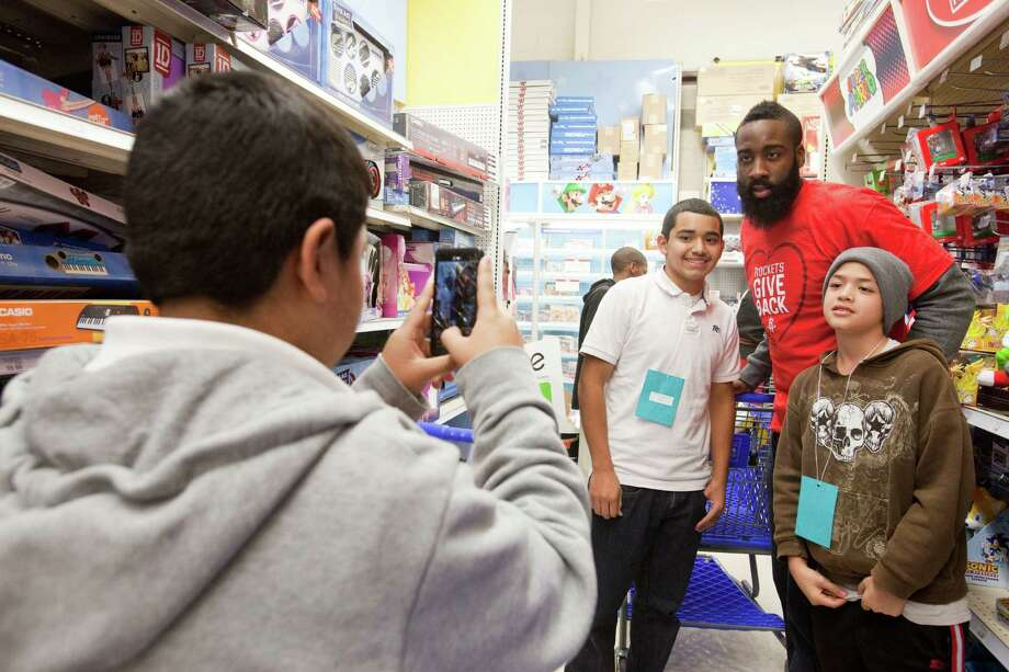 Tony Aguilar, 15, left, photographs Jonathan Bernal, 14, Houston Rockets James Hardin and Jose Salguero, 11, Dec. 11, 2012 in Houston at Toys R Us. Photo: Eric Kayne / © 2012 Eric Kayne