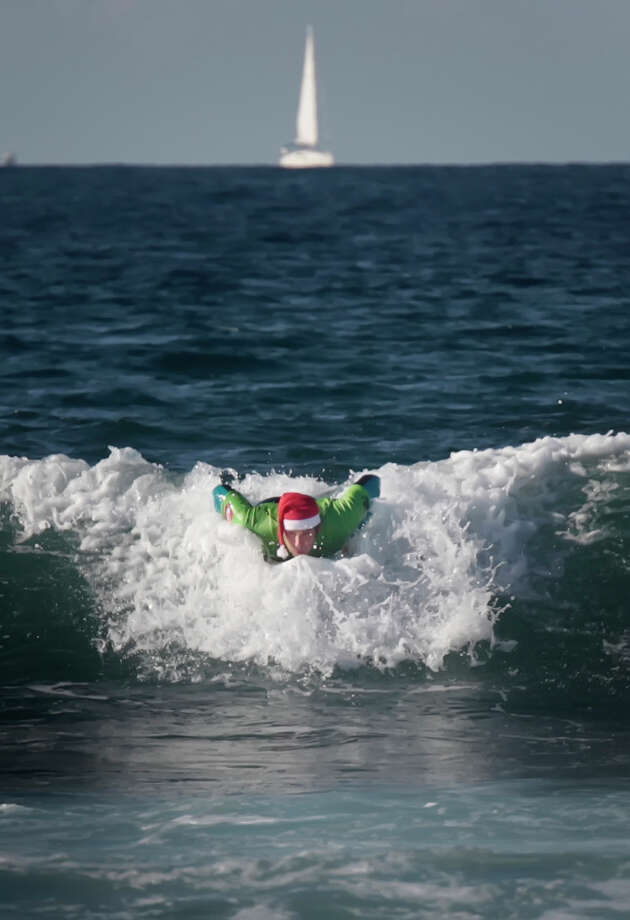 A man wearing a Santa hat practices surf at the beach of Las Americas on the Spanish Canary Island of Tenerife on December 11, 2012. Photo: DESIREE MARTIN, AFP/Getty Images / AFP