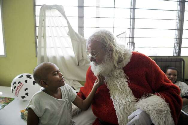 Icelandic philantropist Einar Sveinsson, dressed as Santa Claus, speaks with a patient at the oncology ward during a visit to the Benjamin Bloom National Children Hospital, in San Salvador, on December 11, 2012. Sveinsson visits the hospital prior to Christmas every year since 2001 to give gifts to the patients. Photo: JOSE CABEZAS, AFP/Getty Images / AFP