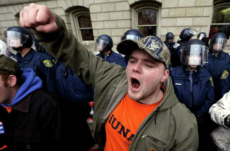 Drew Dobson, of Coleman, Mich., protests at a rally at the State Capitol in Lansing, Mich., Tuesday, Dec. 11, 2012. The crowd is protesting right-to-work legislation passed last week. Michigan could become the 24th state with a right-to-work law next week. Rules required a five-day wait before the House and Senate vote on each other's bills; lawmakers are scheduled to reconvene Tuesday and Gov. Snyder has pledged to sign the bills into law. (AP Photo/Paul Sancya)p Photo: Paul Sancya