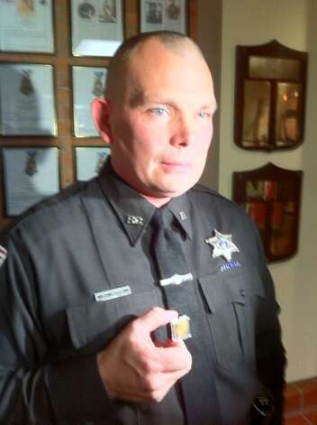 Rensselaer County Deputy Adrian Morin holds a heroism pin presented to him Tuesday by the Rensselaer County Legislature. (Kenneth C. Crowe II/Times Union)