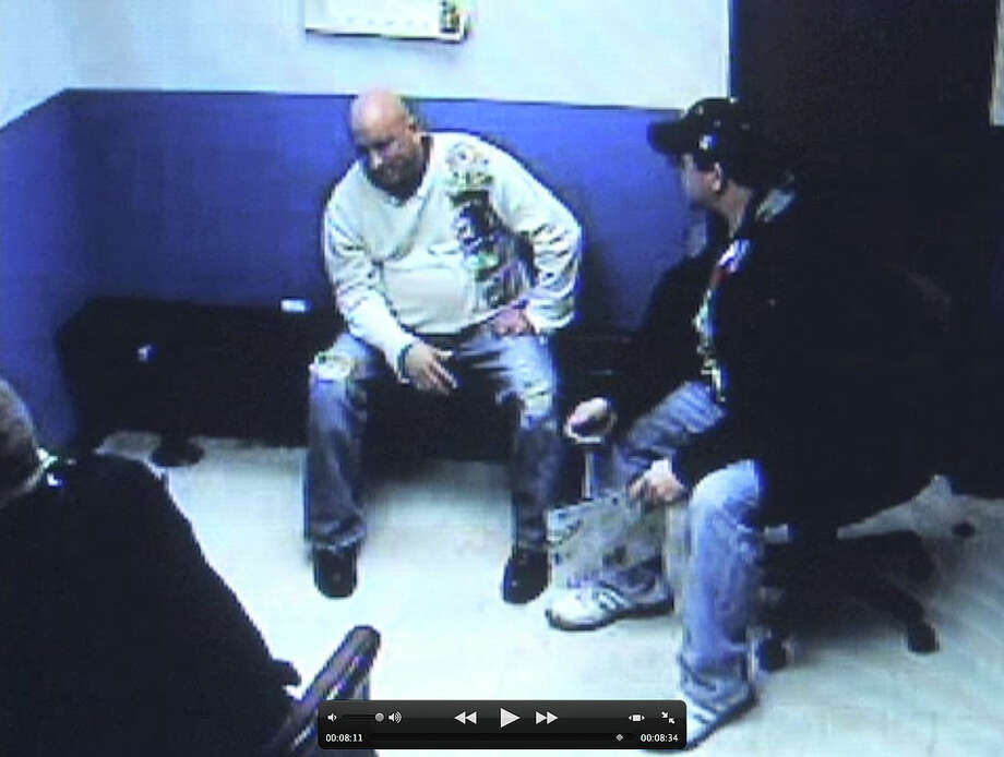 Frame grab from stationhouse video footage of Albany police officer Brian Lutz?s, left, arrest in Menands. Christian Mesley, the former Albany police union president, is pictured right.  (Times Union)