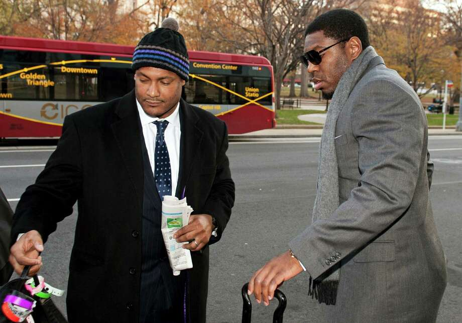 FILE - In this Nov. 30, 2012, file photo, New Orleans Saints football defensive end Will Smith, left, and linebacker Jonathan Vilma arrive at an attorney's office in Washington, for a hearing on their appeals of bounties suspensions. Former Commissioner Paul Tagliabue, who was appointed to handle a second round of player appeals to the league, has informed all parties he planned to rule by Tuesday, Dec. 11, and his decision could affect whether two current Saints — Jonathan Vilma and Will Smith — get to play out the season. (AP Photo/Cliff Owen, File) Photo: Cliff Owen