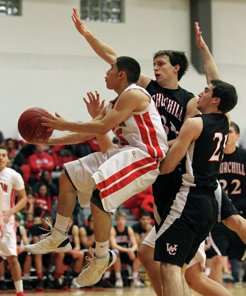 Judson's Julian Erickson (left) takes the ball to the basket against Churchill's Taylor Sutlive (34) and Drake Bigley (21) during their non-district game at Judson on Tuesday, Dec. 11, 2012. Churchill defeated Judson, 57-54.