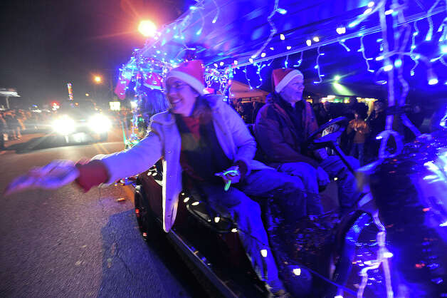 A reveler tosses candy and trinkets at the Nederland Lighted Christmas Parade on Tuesday. Waiting crowds watched as several floats lit up Nederland Avenue.  Photo taken Tuesday, December 11, 2012 Guiseppe Barranco/The Enterprise Photo: Guiseppe Barranco, STAFF PHOTOGRAPHER / The Beaumont Enterprise