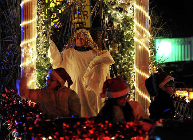 Revelers toss candy and trinkets at the Nederland Lighted Christmas Parade on Tuesday. Waiting crowds watched as several floats lit up Nederland Avenue.  Photo taken Tuesday, December 11, 2012 Guiseppe Barranco/The Enterprise Photo: Guiseppe Barranco, STAFF PHOTOGRAPHER / The Beaumont Enterprise