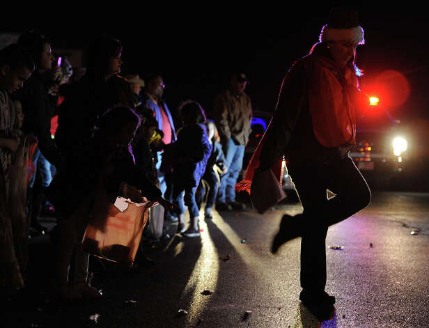 Children scrambled for candy and trinkets during the Nederland Lighted Christmas Parade on Tuesday.  Photo taken Tuesday, December 11, 2012 Guiseppe Barranco/The Enterprise Photo: Guiseppe Barranco, STAFF PHOTOGRAPHER / The Beaumont Enterprise