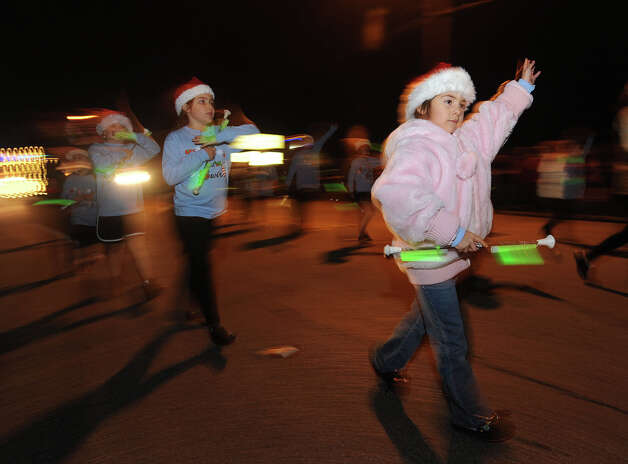 Children parade by at the Nederland Lighted Christmas Parade on Tuesday. Waiting crowds watched as several floats lit up Nederland Avenue.  Photo taken Tuesday, December 11, 2012 Guiseppe Barranco/The Enterprise Photo: Guiseppe Barranco, STAFF PHOTOGRAPHER / The Beaumont Enterprise