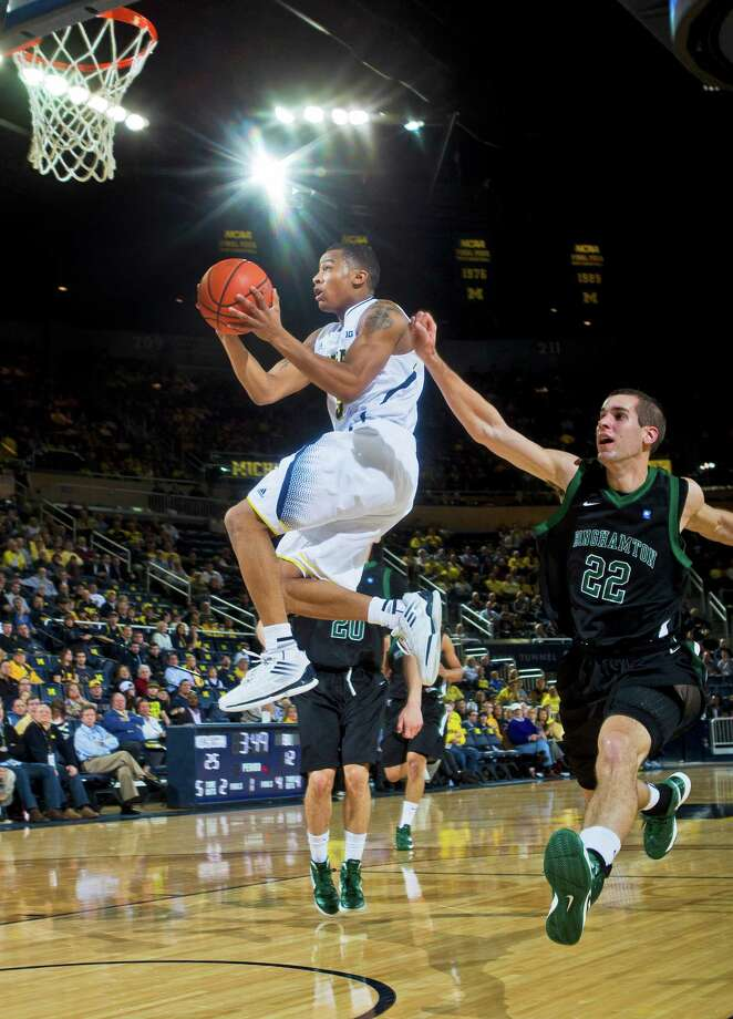 Michigan guard Trey Burke goes up for a basket as Binghamton forward Taylor Johnston (22), trails duringthe first half of an NCAA college basketball game, Tuesday, Dec. 11, 2012, at Crisler Center in Ann Arbor, Mich. (AP Photo/Tony Ding) Photo: Tony Ding