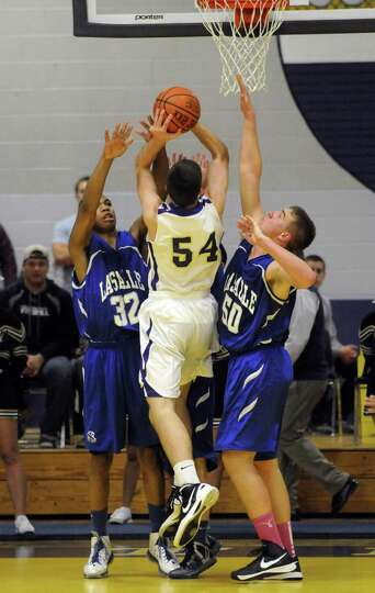 CBA's Greig Stire is met by a wall of defense as he goes to the basket during their boy's high schoo