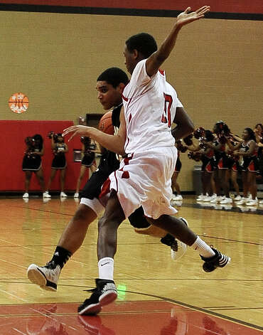 Nederland guard Diondre Frank, #21, drives past Memorial guard Ron Taylor, #10, during the Memorial High School basketball game against the Nederland High School on Tuesday December 11, 2012, at Memorial High School. Nederland won over Memorial 42- 41. Photo taken: Randy Edwards/The Enterprise