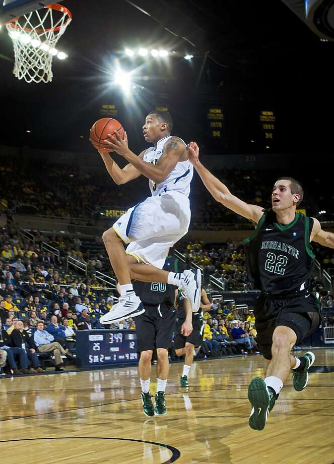 Michigan guard Trey Burke elevates past Binghamton forward Taylor Johnston. Photo: Tony Ding, Associated Press