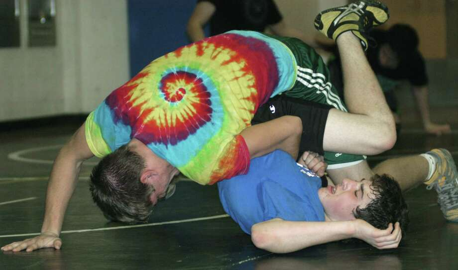 The Green Wave's Kameron Bradshaw schools Brett Leonard as they work on their moves during pre-season practice for New Milford High School wrestling. December 2012 Photo: Norm Cummings
