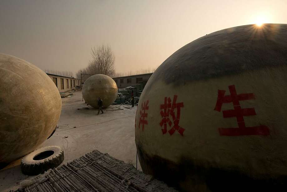 Survival pods dubbed 'Noah's Arc' by their creator, farmer Liu Qiyuan, stand in a yard at his home in the village of Qiantun, Hebei province, south of Beijing on December 11, 2012. Inspired by the apocalyptic Hollywood movie '2012' and the 2004 Asian tsunami, Liu hopes that his creations consisting of a fibreglass shell around a steel frame will be adopted by government departments and international organisations for use in the event of tsunamis and earthquakes. Liu has built seven pods which are able to float on water, some of which have their own propulsion. The airtight spheres with varying interiors contain oxygen tanks and seatbelts with space for around 14 people, and are designed to remain upright when in water. Photo: Ed Jones, AFP/Getty Images