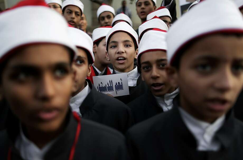 "Supporters of Egyptian President Mohammed Morsi, from Al Azhar schools chant slogans during a demonstration in Cairo, Egypt, Tuesday, Dec. 11, 2012. Islamists led by Morsi's Muslim Brotherhood group have called a demonstration to back the president's decision to hold a referendum on the new constitution on December 15. Opposition groups have rejected the constitution as undemocratic and want the vote canceled. Arabic on the paper reads, ""yes to the constitution."" (AP Photo/Hassan Ammar) Photo: Hassan Ammar, Associated Press"