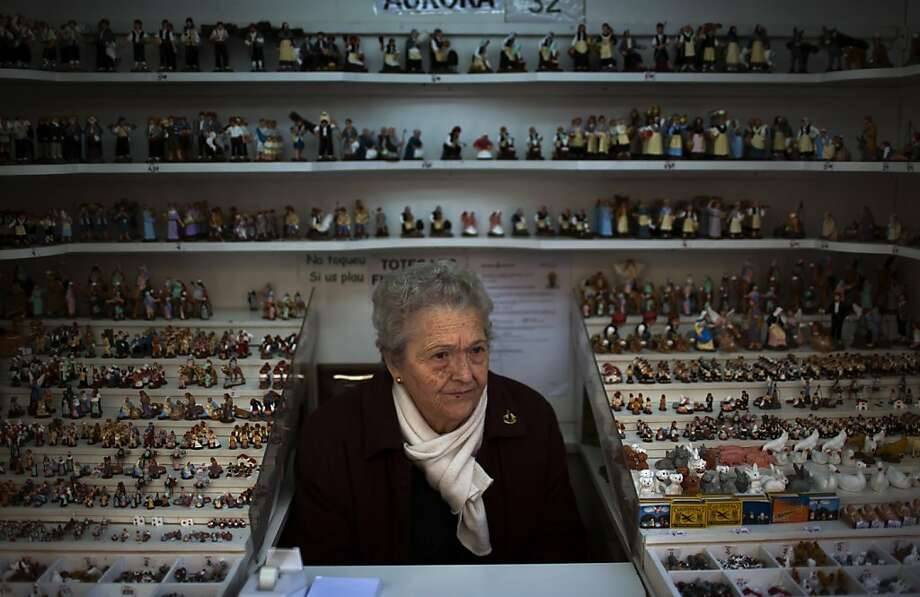 Aurora waits for customers at her shop selling figures to decorate the Christmas crib, in Barcelona Spain, Tuesday, Dec. 11, 2012. Spain came under renewed pressure to seek help Monday as its secondary market borrowing costs — a measure of investor wariness — rose after Italian Premier Mario Monti's decision to resign caused market jitters. Photo: Emilio Morenatti, Associated Press