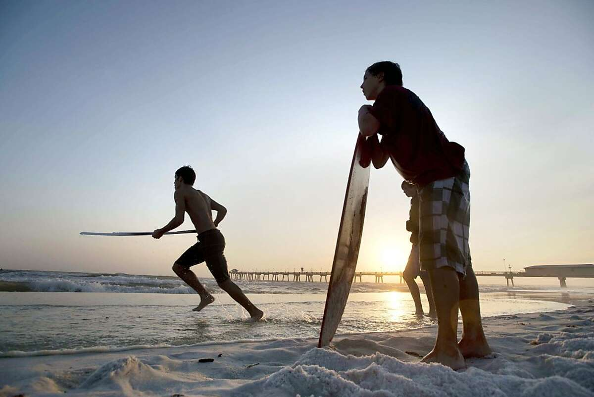 10. Fort Walton Beach, Fla. In this photo, Cole Jarski, right, and Tyler Chastain take advantage of warm weather and windy surf to skim board behind the Boardwalk on Okaloosa Island in Fort Walton Beach, Fla., Monday, Dec. 10, 2012 evening.