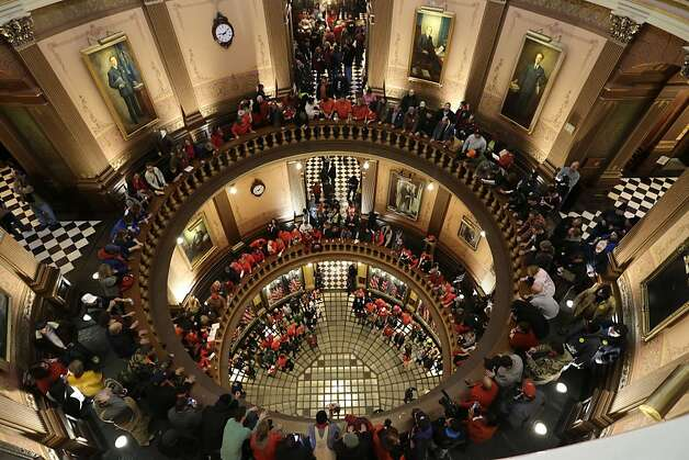 Protesters gather for a rally in the State Capitol rotunda in Lansing, Mich., Tuesday, Dec. 11, 2012. The crowd is protesting right-to-work legislation passed last week. Michigan could become the 24th state with a right-to-work law next week. Rules required a five-day wait before the House and Senate vote on each other's bills; lawmakers are scheduled to reconvene Tuesday and Gov. Snyder has pledged to sign the bills into law. (AP Photo/Paul Sancya) Photo: Paul Sancya, Associated Press
