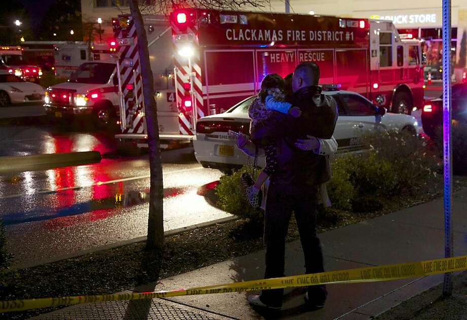 A couple with a child embrace after they were released from the mall at Clackamas Town Center in Portland, Ore., Tuesday, Dec. 11, 2012. Witnesses say the scene went from cheery to chaotic in seconds when a gunman opened fire in the suburban Portland shopping mall Tuesday, killing two people and wounding another. Photo: Thomas Boyd, Associated Press