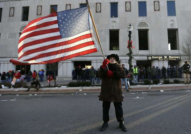 Protester Paula Merwin, of Leslie, Mich., stands with an American flag outside the George W. Romney State Building, where Gov. Snyder has an office in Lansing, Mich., Tuesday, Dec. 11, 2012. The crowd is protesting right-to-work legislation passed last week. Michigan could become the 24th state with a right-to-work law next week. Rules required a five-day wait before the House and Senate vote on each other's bills; lawmakers are scheduled to reconvene Tuesday and Gov. Snyder has pledged to sign the bills into law. (AP Photo/Paul Sancya) Photo: Paul Sancya, Associated Press
