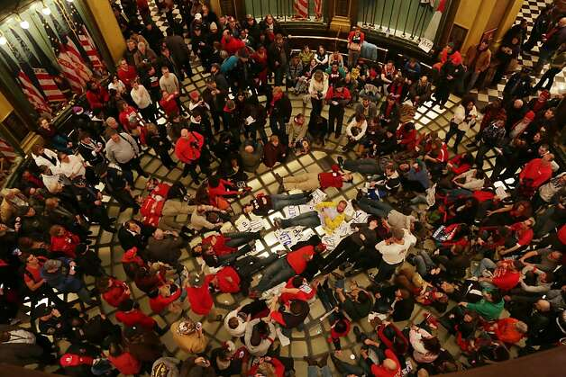 A crowd of protestors sit in inside the state Capitol against two controversial right-to-work bills that the Michigan House of Representatives passed in Lansing, Mich. on Tuesday Dec. 11, 2012. As chants of angry protesters filled the Capitol, Michigan lawmakers gave final approval Tuesday to right-to-work legislation, dealing a devastating and once-unthinkable defeat to organized labor in a state that has been a bastion of the movement for generations. (AP Photo/Detroit Free Press, Romain Blanquart)  DETROIT NEWS OUT;  NO SALES Photo: Romain Blanquart, Associated Press